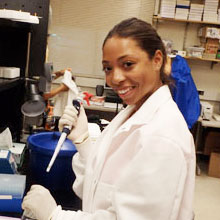 woman in a lab coat and a pipette