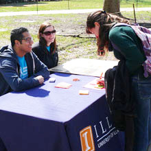 students sitting at information table on the Illinois main quad
