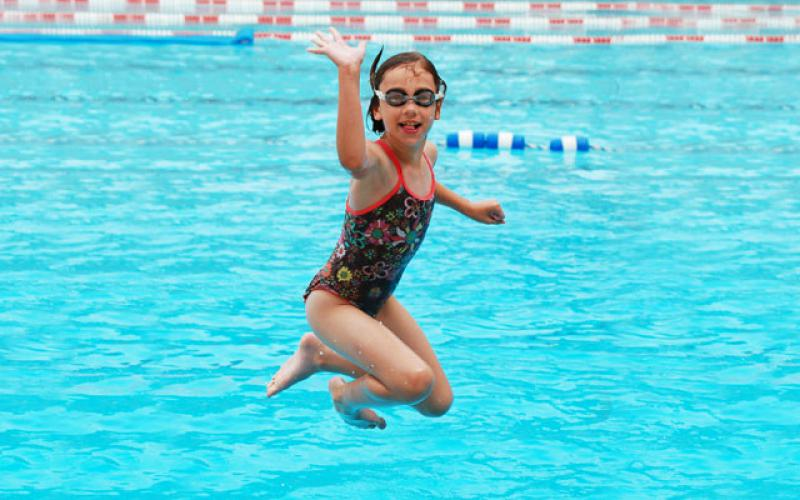 8-year-old girl waving as she jumps into a swimming pool.